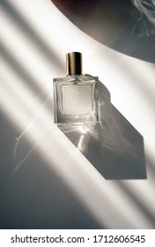 glass perfume bottle with shades from the sun on a white background