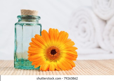 A glass phial and a sunflower with white towels on the background