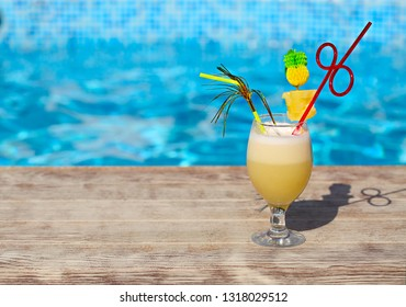 Glass of pinacolada cocktail standing on the swimming pool ledge in an tropical resort