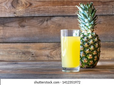 Glass of pineapple juice with fresh pineapple on the wooden background