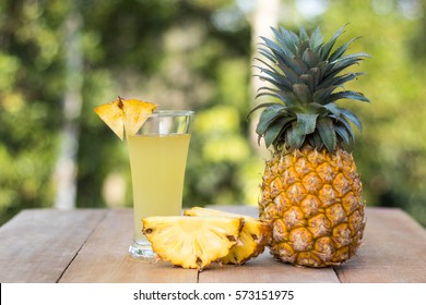 glass of pineapple juice with green nature background