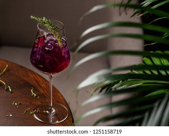 Glass of pink alcohol cocktail with thyme