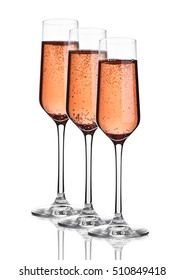 Glass of pink rose champagne with bubbles on white background with reflection