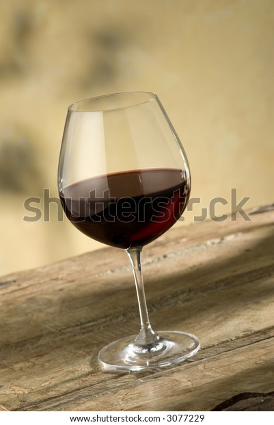 glass of pinot noir wine on rustic wooden table, warm colored background,nice red glow in glass