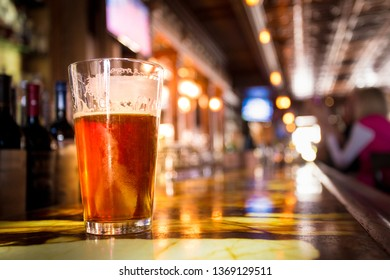 Glass Pint of amber beer with colorful blur of bar in background