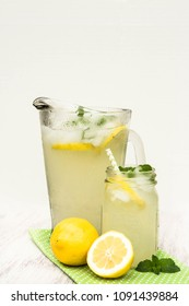 Glass pitcher and jar of lemonade with lemons on white background in summer vertical