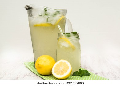 Glass pitcher and jar of lemonade with lemons on white background in summer