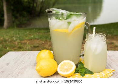 Glass and pitcher of lemonade outside by the lake in summertime