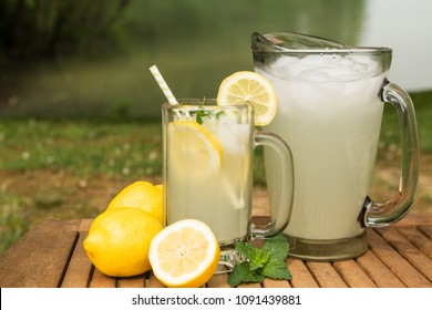 A glass and pitcher of lemonade outside next to the lake in summertime