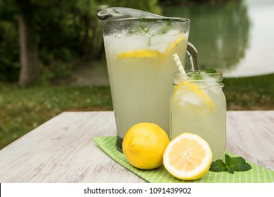Glass pitcher and mug of lemonade with lemons on white wood table outside by the lake in summertime