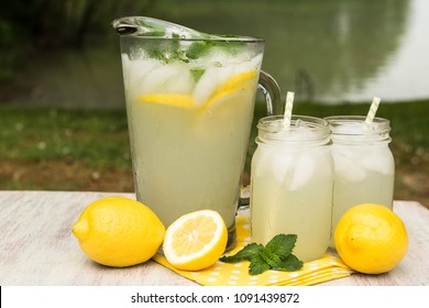 Glass pitcher and mugs of lemonade with lemons and mint outside by the lake in summer