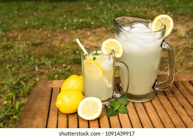 A glass and pitcher of tasty lemonade is a great treat on a hot summer day outside