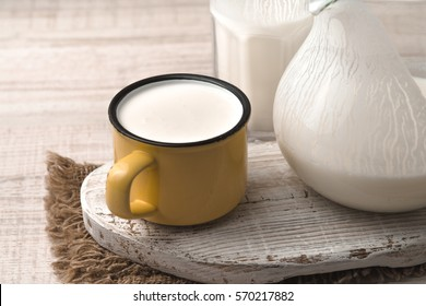 Glass, pitcher, yellow cup of kefir on the napkin and white stand horizontal