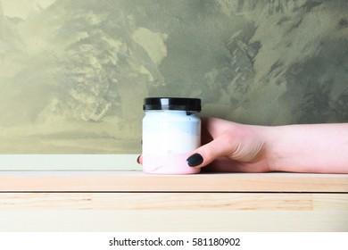 glass or plastic jar with lotion, cream or bath salt white color for spa salon as health care in female hand on wooden board on grey textured wall background, copy space