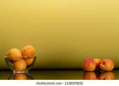 a glass plate with apricots and apricots on the table, surface reflection, yellow gold background, side view