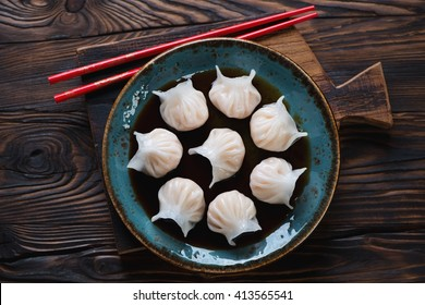 Glass plate with dim-sums in soy sauce, rustic wooden setting, top view
