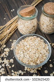 A glass plate of dry oat flakes or oat grains with oat spikes or spikelets on dark rustic wooden background