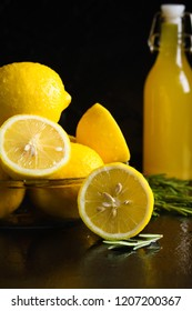 Glass plate of fresh sliced lemons rosemary bottle with lemon drink juice homemade limoncello on black wooden background. Cooking, kitchen concept.