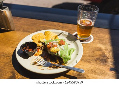 Glass plate on wooden table with burrito, chips, salsa, and a half-drank pint of beer. Outdoor daytime setting.