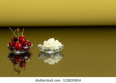 a glass plates with kefir grain sand red cherries and surface reflection, gold background