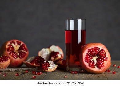 Glass of pomegranate juice on a wooden surface. Closeup