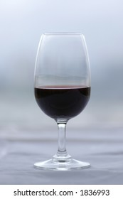 A glass of Port (Vinho do Porto) on a white surface, against a muted green/grey background