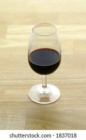 A glass of Port (Vinho do Porto) sitting on a butcher block surface