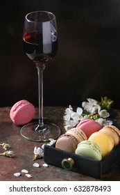 Glass of port wine with variety of colorful french sweet dessert macaron macaroons with different fillings served with spring flowers over dark texture background. Celebration concept