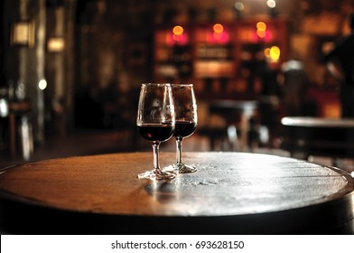 Glass with portuguese 10 year old tawny porto wine standing on the barrell in the restaurant in vineyard, Porto, Portugal