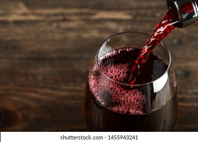 in a glass pour red wine, on a wooden background, space for text