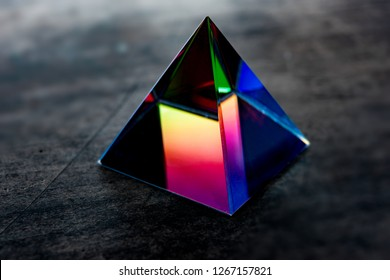Glass prism or pyramid Refracting light in vivid rainbow colors. Refractions of light in a glass prism. Focus is on front edge.