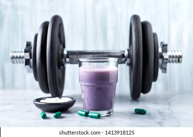 Glass of Protein Shake with milk and blueberries, Beta-alanine and L-Carnitine capsules and a dumbbell in background. Sports bodybuilding nutrition. Stone / Wooden background. Copy space.