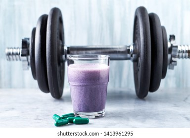 Glass of Protein Shake with milk and blueberries, L-Carnitine capsules and a dumbbell in background. Sports bodybuilding nutrition. Stone / Wooden background. Copy space.