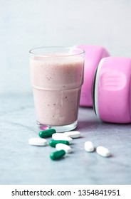 Glass of Protein Shake with milk and raspberries. BCAA amino acids, L - Carnitine capsules and pink dumbbells in background. Sport nutrition. Stone / Wooden background. Copy space.