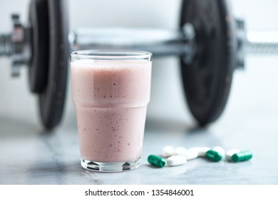 Glass of Protein Shake with milk and raspberries. BCAA amino acids, L - Carnitine capsules and a dumbbell in background. Sport nutrition. Stone / Wooden background. Copy space.