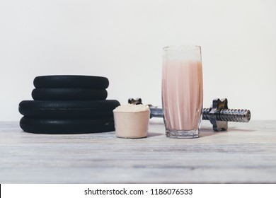 Glass of protein shake next to portion of dry powder in measuring scoop and metal dumbbell. Sports drink and heavy weights.