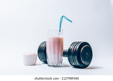 Glass of protein shake with a straw next to a portion of dry powder in a scoop and dumbbell. Sports drink and heavy weights.