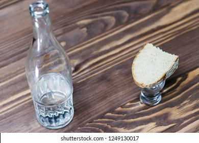 a glass of pure alcohol, a bottle and a piece of bread and cheese on a wooden background. a glass and on it a red cross. concept of quit drinking. there is toning.