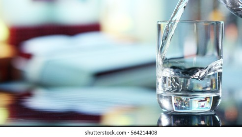 A glass of pure fresh water is poured into a glass, the background bedroom, nature, from which the fresh and pure water. Concept: nature, purification, freshness.