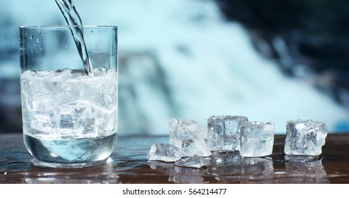 A glass of pure fresh water is poured into a glass, the background waterfalls, nature, from which the fresh and pure water. Concept: nature, purification, freshness.