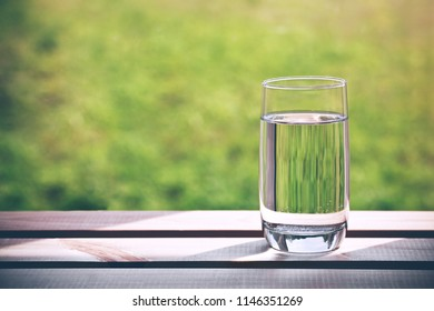 Glass of pure water on green natural background. Space for text