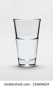 Glass of pure water on light gray background. The glass is half-full or half-empty.