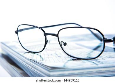 glass put on magazine stack close up