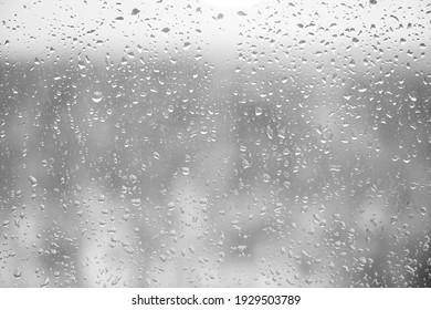 Glass with rain drops against gray background.