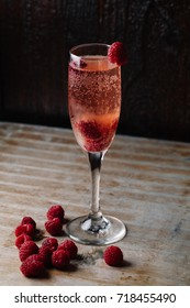 A glass of raspberry champagne on rustic background