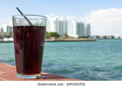 Glass of real soft drink ; on background Miami skyline