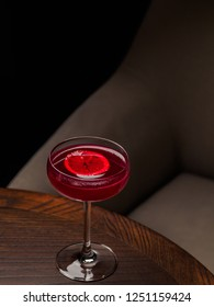 Glass of red alcohol cocktail with lemon slice on a table