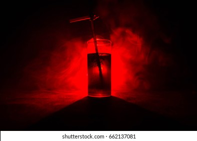 Glass of Red Alcoholic Cocktail on Dark Background with smoke and backlight. Fire hot coctail