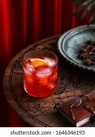 ein Glas roter Cocktail mit einer Scheibe Orange auf einem Holztisch in einem exotischen Ambiente
