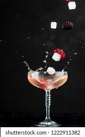 glass of red coctail with red fruits on black background, visible splashes, drops and movement of the liquid